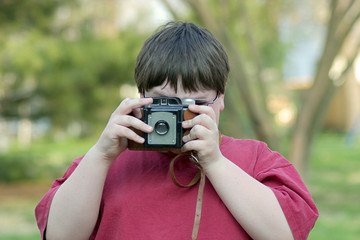 boy taking picture with old camera