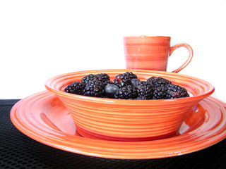 mixed berries in orange bowl with cup