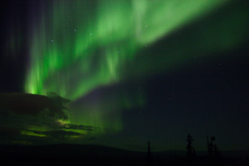 aurora dance in the cloudy sky