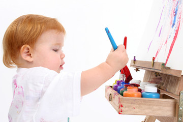 adorable baby girl painting at easel