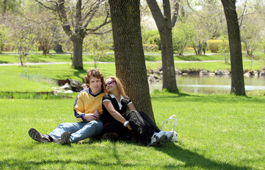 romantic couple sitting in a park.