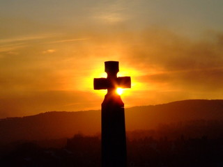 cross agianst a setting sun