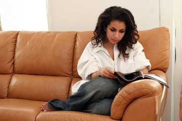 teenage girl reading a magazine on a sofa