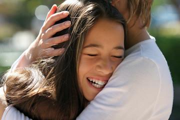 mother hugging her happy daughter