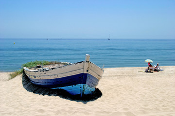 old rowing boat on white sandy beach and people sunbathing next
