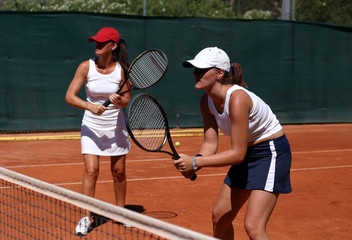 two fit, young, healthy women playing doubles at tennis in the s