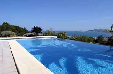beautiful blue fresh infinity swimming pool in a villa in sunny