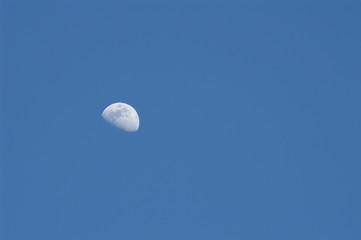 three quarter moon on medium blue sky