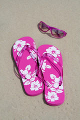 flip-flops and sun glasses on the sand
