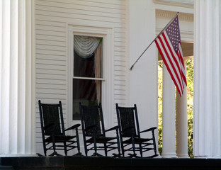 three rocking chairs on porch with flag