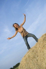 pretty girl standing on bale of hay stressing out