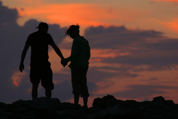 silhouette of couple walking in front of sunset