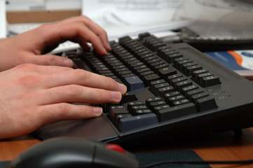 a man in an office typing on a keyboard