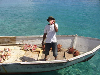 man selling conch shells in boat in nassau, bahama