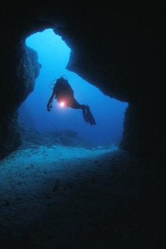 plongeur à l'entrée d'une grotte sous-marine