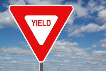 yield sign with clouds