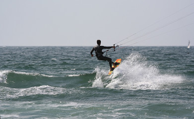 kitesurfer with a sail boat