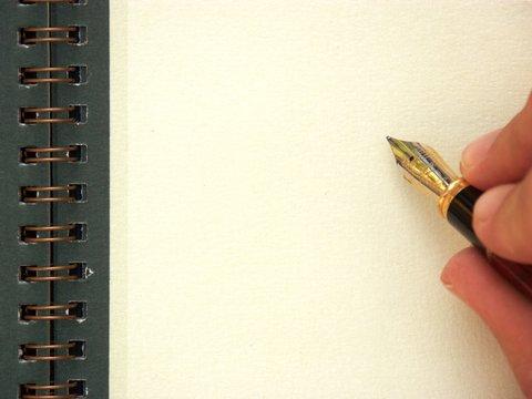 main et stylo écrivant sur une page blanche