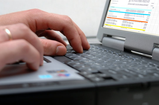 man's hands on the keyboard of laptop
