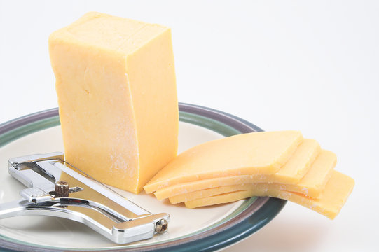 cheddar cheese and a cheese slicer