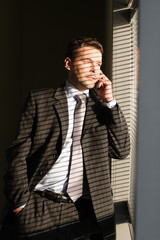 business man on phone  looking through window blin