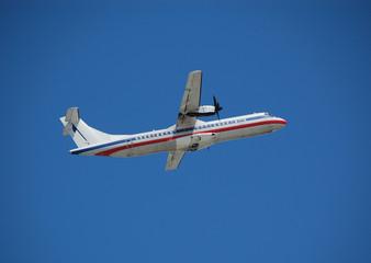 white turboprop airplane aginst blue sky