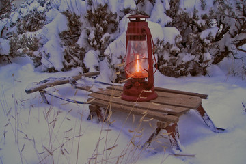 oil lamp on an old sled in snowy winter evening