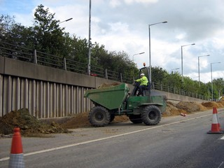 dumping earth with a dumper truck in road works/co