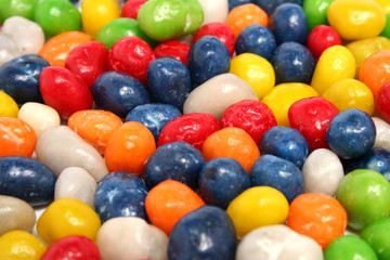 horizontal background made of multi-coloured sweets with raisin