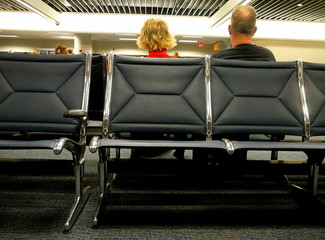 a man and woman in the waiting area at the airport