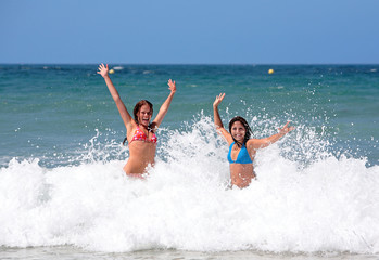 two attractive young girl friends playing in the s