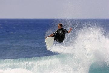 surfer executing an ariel maneuver