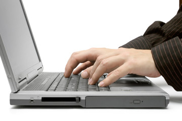 typing on a grey laptop.