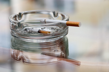 ashtray with cigarette on a reflecting surface of a glass table