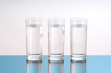 three glasses of water with reflection