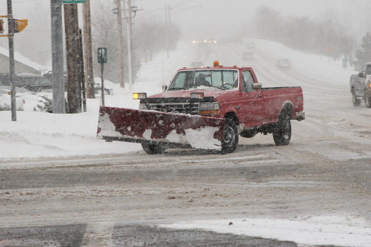 snow plow driving on snow covered street