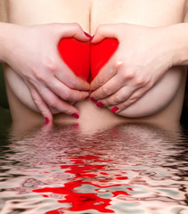 female breasts and heart symbol made from hands