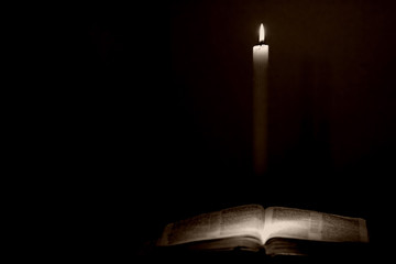 holy bible lit by a candle