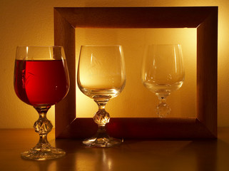 glass with wine at light of candles.
