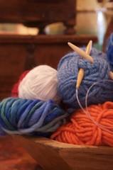 knitting balls of yarn in wooden bowl