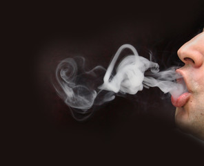 man blowing smoke with black background