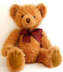 teddy bear with red bow sitting