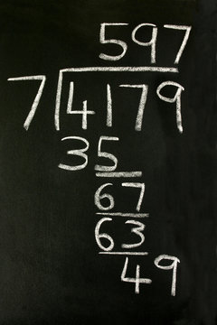 a long division sum on a blackboard.