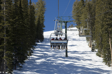 skiiers riding chairlift