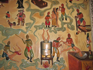sculpted and painted wall in a buddhist temple showing torture,