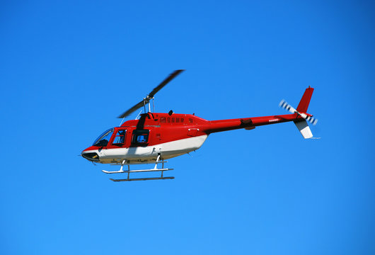 red helicopter in flight bell 206