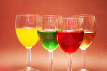 glasses with drinks of various colours on biege ba