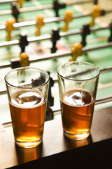 two glasses of beer at foosball table.