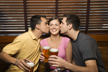 two men kissing young woman in middle.