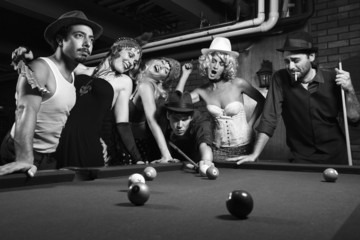 retro group trying to distract man as he takes pool shot.
